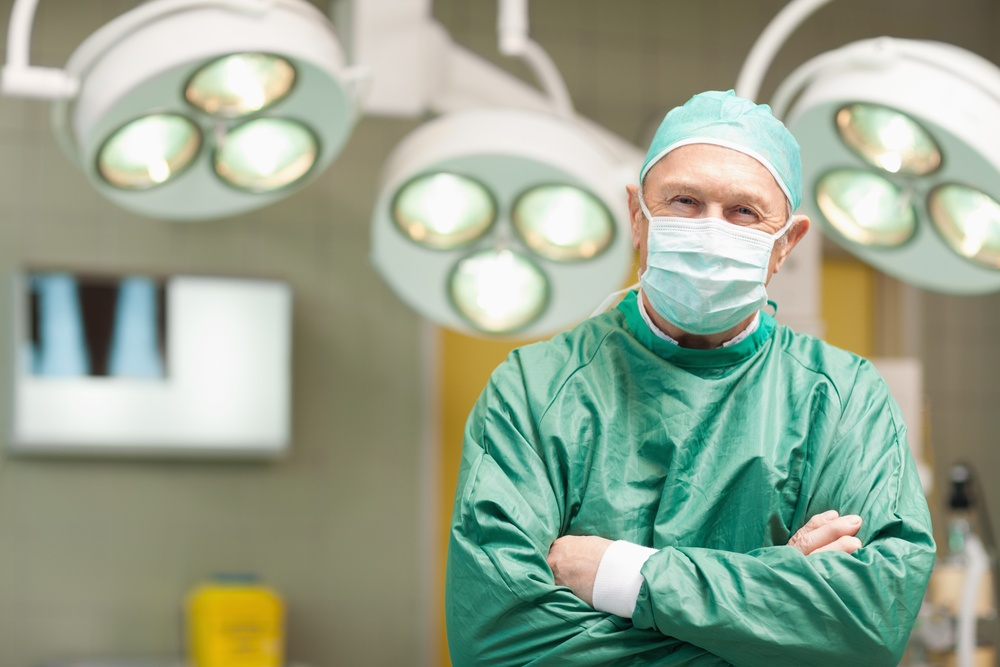 Smiling surgeon crossing his arms while standing in a surgical room